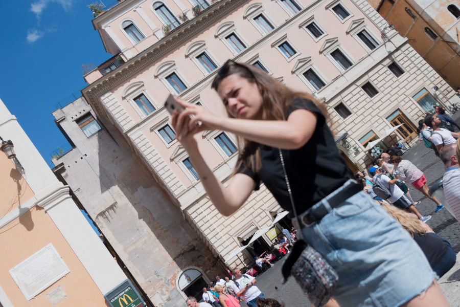 tourist taking a photo in Rome Italy with her phone